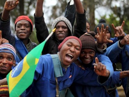 Trabalhadores de Johannesburgo, orgulhosos, seguram a bandeira do Brasil. A seleção brasileira foi adotada como segundo time na África do Sul