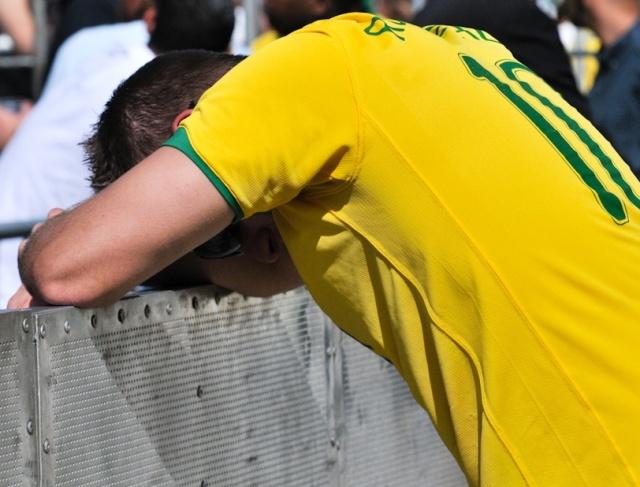 Torcedor triste apoia-se em grade por causa da derrota brasileira nas quartas de final